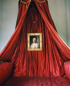 Dans une petite chambre, sur le baldaquin de soie rutilante d'un lit Louis XV est accroché un portrait de femme, école italienne, du XVIIIe siècle.