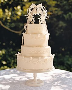 A cake topper derives its super-sweet charm from two wedding bells made with quilling paper and framed by vintage millinery lily-of-the-valley buds and a gauzy vintage linen ribbon, tied into a bow; festooned with rose-budded swags of royal icing, the raspberry-lemon cake rests with ladylike poise on a pedestal.