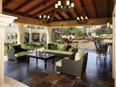 Beautiful outdoor living space.  Love the green against that brown tile floor.  Lighting fixtures are lovely.
