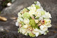 Bride's Bouquet: hand-tied, textured nosegay with depth; stems wrapped completely with ivory satin ribbon. Flowers: ivory and crème seasonal blooms with accents of soft sherbet and lime using peonies, ranunculus, dahlias, roses, hydrangea,  vibernum and Blushing Bride protea (if available) with details of pearls and rhinestones.    www.meganhaneydesigns.com