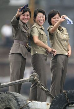 Female North Korean soldiers wave to a Chinese boat for tourists on the banks of Yalu River near the North Korean town of Sinuiju July 27, 2010.