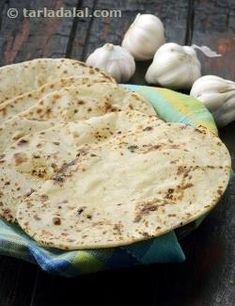 This is a rich Indian bread recipe, with the exciting flavour of garlic and green chillies. Handle the dough carefully, just as explained in the recipe in order to get the perfect texture of naan. While naan is traditionally prepared in a tandoor, this Butter    Garlic Naan can be comfortably prepared in a tava at home.