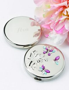 Dancing Butterfly Compact Mirror made of nickel plated metal with a high polish finish. The top cover is embossed with three butterflies and a floral accent. The butterflies are decorated with blue, purple, and clear rhinestones. Inside there are two mirrors.  The bottom of the compact can be personalized.