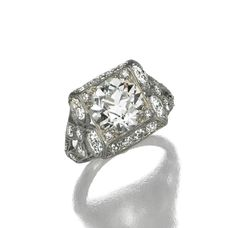 DIAMOND RING, CIRCA 1925.  The round diamond weighing 3.20 carats, within a squared panel, the openwork shoulders decorated with bow motifs, set with numerous small round diamonds, mounted in platinum