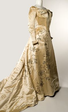 Two piece satin wedding gown with a basque bodice with horizontal tucks, and trimmed with sequins, beads and pearls. (1898) Made by the Slater Sisters, St. Louis. Mary Slater worked out of her home as a dressmaker before moving her business to Washington Avenue in 1893. Several years later her sister Grace joined her in the business, which specialized in hats and wedding and evening gowns. Missouri History Museum