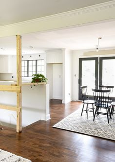 An open floor plan of a ranch style home with white craftsman style columns and black modern railing. One Wall Kitchen, Stairs In Kitchen, Kitchen Redo, Kitchen Living, Open Basement Stairs, Craftsman Style Decor, Modern Railing, New Staircase, House Siding