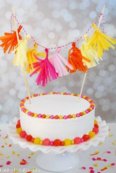 Tutorial: Mini Tissue Tassel Garland + plain white cake from Walmart, decorated with pearl Sixlets (small) and Sour Balls (large) candies   {Paisley Petal Events}