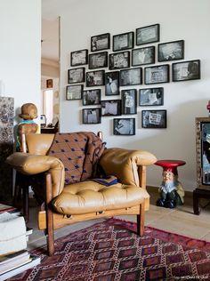 Poltrona Mole, tapete étnico e parede com composição de quadros em preto e branco.