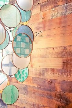 Embroidery hoops, colorful thin fabric, suspended in front of windows.  Beautiful... by THELMA TOFANI