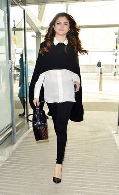 Selena Gomez makes her way into the airport in a polished yet comfortable outfit.  The star wore a white button down, a sweater cape, and a pair of leggings for a no fuss flying outfit