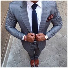 Consider pairing a grey striped suit with a white dress shirt for a sharp, fashionable look. Dress down this getup with brown leather tassel loafers.   Shop this look on Lookastic: https://lookastic.com/men/looks/suit-dress-shirt-tassel-loafers/18849   — White Dress Shirt  — Navy Knit Tie  — Dark Brown Pocket Square  — Grey Vertical Striped Suit  — Dark Brown Leather Watch  — Black Leather Belt  — Brown Leather Tassel Loafers