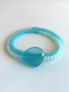 This sea glass wrap bracelet features frosted beads in soft sea foam green and turquoise. The focal bead is frosted turquoise beach glass. The shiny sterling si