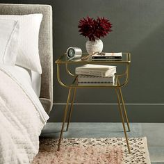 Sleek and streamlined in glass and antique brass-finished metal, our Frankie Bedside Table brings mid-century style to the bedroom with its retro silhouette.