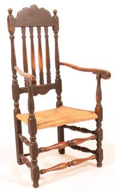 "Conestoga Auctions -  Harry B. Hartman Estate Auction - Session VI  Nov. 21, 2015.  Lot: 745.       Estimate:	$300 – $500.  Sold: $826.     Description:   American 18th Century Banister Back Armchair. Shaped crest rail, turned finials, scrolled arms with turned supports, woven rush seat, turned stretchers, old dark green painted surface. Seat height 16""h.; 46""h. overall. Condition: Good, with age wear, feet have been reduced, rush seat probably old replacement."