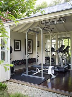 Outdoor garage gym with really cool door for feeling like you're working out outside. Dream home gym decor: dream home garage gym design.