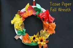"Fall wreaths. We used paper plates with the centers cut out as the base for our wreaths. tear a piece of brown construction paper into strips.  These strips were supposed to look like branches.  Once the ""branches"" were glued around the wreath, we crumpled 3×3 inch squares of fall coloured tissue paper and glued those on. Use a low-heat glue gun  to attach the leaves/branches."