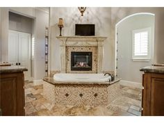 Spa master bathroom // Walk in shower behind the soaker tub with a fireplace, dual vanities, walk in closet