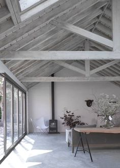 The living room at the Cow Shed, a Victorian barn conversion by Nash Baker Architects in Suffolk, showing the vaulted ceiling with exposed lime washed timber roof trusses, and the wood burning fieplace. Photo by Nick Guttridge Roof Beam, Timber Roof, Roof Trusses, Timber Ceiling, Open Ceiling, Floor To Ceiling Windows, White Ceiling, Exposed Trusses, Cow Shed