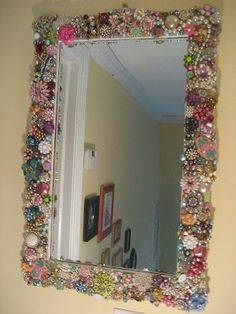 Old, mismatched , or bits of broken Costume Necklaces, Brooches, Earrings etc... glued on a Mirror or Picture Frame. Thrift stores and Second Hand stores have some if you need them. by gertrude