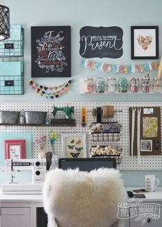A beautiful, colorful craft room office wall with pegboard for storage, baskets, DIY garlands, art and hanging mason jar storage.
