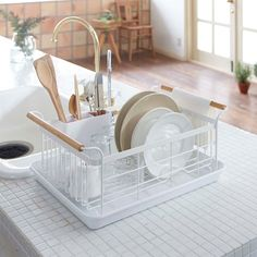 This simple drainer rack by Yamazaki fits in next to any sink and is self draining. It can hold any variety of plates, bowls, dishes, utensils or glasses that need drying, and it has a small tube on the bottom that drains all excess water right into the sink.