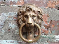 """Vintage Lion Doorknocker. I bought mine in Portobello Road when I was a teen. I've been waiting for that """"special cottage"""" to hang it on. Lion's head doorknockers were intended to serve the same symbolic function as the lion statues which decorated the gates of ancient Greek gates. These intimidating lions served as guardian beasts for the city, as well as symbolizing strength & power. The same thing can be said for lion's head doorknockers, which rest on doors as guardians of a building."""