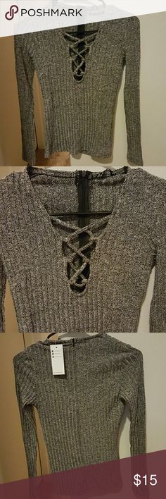 Lace up top New with tags! size small. Ribbed & stretchy sweater-like material. Super flattering fit. Comes with a concealed zipper in the back as shown in the last pictures. Color is a marled dark gray. Not from forever 21; listed for exposure Forever 21 Tops Tees - Long Sleeve