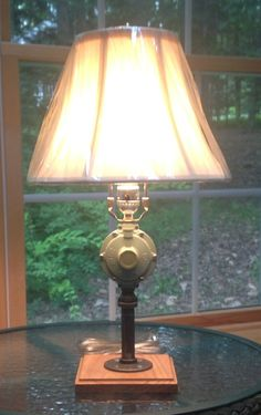This lamp was made from a propane regulator that that I found at a second hand store. It is mounted on black iron piping attached to a Red Oak base. Warm light without the flame! www.etsy.com/shop/Lampsbyjohn