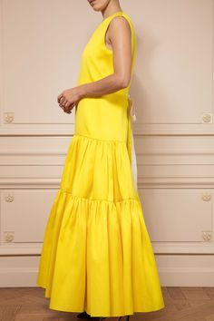 df8f01141d3 ... sleeveless gown is cut from heavyweight canary yellow satin. The  gathered and tiered skirt falls into softly draped pleats from the drop  waist