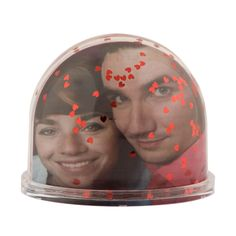 A snow globe with small red hearts inside.