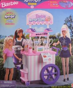 """Barbie Kool-Aid Soft Drink Stand Playset w Working Drink Dispenser (1997) by Mattel, made in Mexico. $129.99. Barbie Kool-Aid Soft Drink Stand Playset is a 1997 Mattel production, made in Mexico. (Sun Glasses & Visors made in China & Kool-Aid made in USA).. For Ages 3+ Years. NO DOLLS included. Box approx. 13"""" x 10-1/2"""" x 5"""". Sizes & details are approximate & may vary.. Three 2 Quart Envelopes of Kool-Aid Flavors (Net Wt. 0.48 oz.): Roarin' Raspberry Cranberry, Soarin' S..."""
