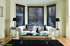 Luxury black wooden venetian blinds in a contemporary living room with white leather sofa, black rug and mirrored tables.