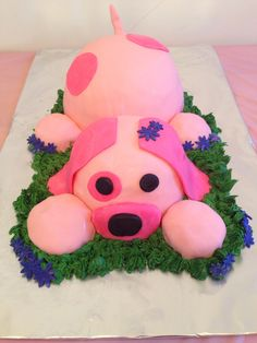 Pink dog cake with green grass and blue flowers