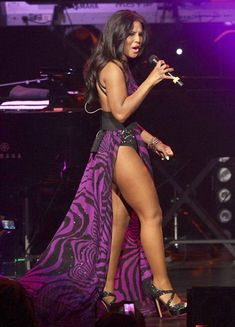 Toni Braxton performing on stage in Purple hot dress.
