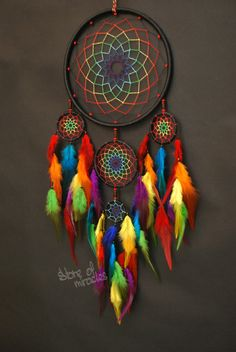Dreamcatcher Tengekvunu which translated from the Native American language means Rainbow Size: diameter of ring: 19 cm, 8 cm, 5 cm, 4 cm (Inches: 7,5; 3,2; 2; 1,5) The length of 57cm (Inches: 22,4) Materials used: Cotton yarn, satin ribbon, feathers, rooster feathers, wooden beads.