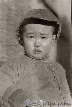A child dressed in winter coat with a runny nose poses for the camera on a Tientsin street in 1946. Harold Giedt Collection.