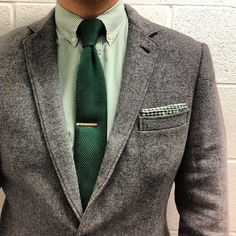 Grey tweed jacket, green gingham shirt, green tie.
