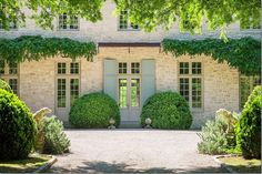 French blue shutters, stone, gravel, and boxwoods gives the house its Provencal look.  Twin concrete dogs greet visitors.