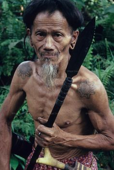 1989: Nomadic Penan native with blowpipe, wispy beard and mustache. Belaga district, Sarawak, Borneo