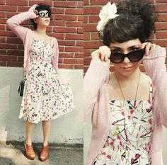 Pretty in a whimsical graphic dress and pink sweater