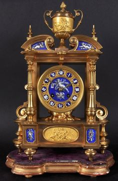 A 19TH CENTURY GILT BRONZE CLOCK, with two-handled cup surmount, the clock with blue porcelain panels of cupids and trophies. 15.5 inches high, on a gilt stand.