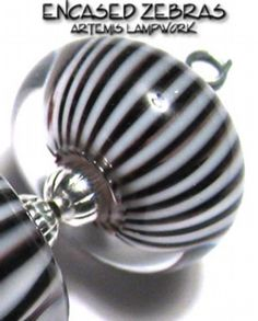 I make my Zebra beads WITHOUT using clear on both sides of the lolly!   First importance is to make the twists TIGHT on your twisty. Next, put a small layer of CLEAR down on your mandrel, then apply your twisty by PUSHING it onto the clear base, don't let it stretch when applying it.  IF I used, for instance, a White base, then stacked Transparent DARK colors, you'd see a pleat instead of the black stripes! (Oh and you'd probably not want to make the clear coat as thick as I have)!
