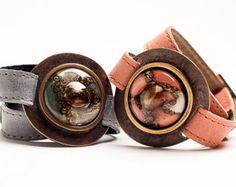 Pulseras únicas hechas con suave cuero de Argentina y vitrofusión pintado a mano. su brazalete es 1.0 amplia y ajustable con dos broches de presión de 7.5 y 8.5 Utilizamos el más moderno método de fusión para una capa de finas láminas de vidrio, pintado a mano con una variedad de colores para crear patrones y dibujos originales. Durante el proceso de fusión en el horno, el vidrio cobra vida y adquiere un nuevo carácter, como las llamativas burbujas comienzan a subir. Las piezas de vidrio…