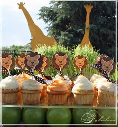 "Wheatgrass ""grassland,"" platform of Plexiglass on green apples and cupcakes with paper lion toppers.  Manes are corrugated brown paper."
