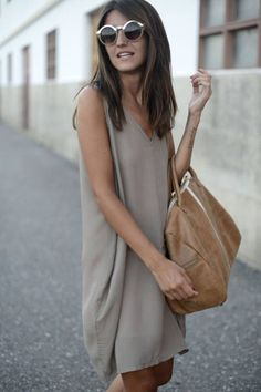 tan shift dress, leather bag and big glasses.