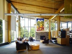 Canada's Whistler Public Library reading room feels warm and inviting thanks to high ceilings, golden wood beams, a stone fireplace, and the open floor plan.
