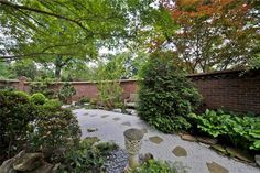 Secret Garden path with rocks, pavers and bench. Brick walls hide.