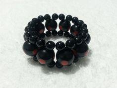 Pulseira confeccionada em fio de silicone com pérolas pretas 8mm e bolas pretas 16mm em resina com detalhe vermelho.