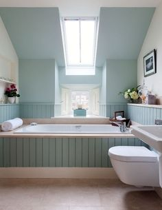 This duck egg blue used on the ceiling, walls and panelling lengthens the room by drawing the eye out through the windows.