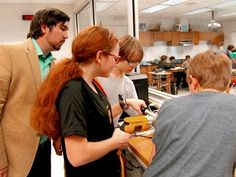 Teacher and students gathered around looking down at a project